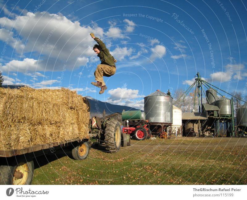 Man Sky Blue Red Joy Clouds Far-off places Jump Playing Freedom Farm Farmer Americas Canada Human being Tractor