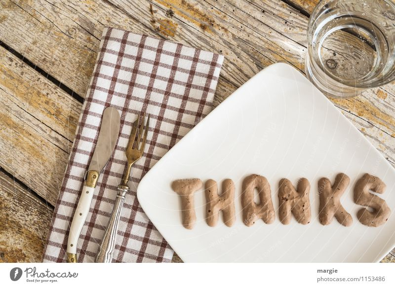 The letters THANKS on a plate with napkin, knife and fork and water glass on a rustic wooden table Nutrition Fast food Finger food Cold drink Drinking water