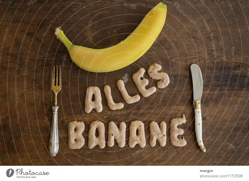 The letters ALL BANANANE with a banana and knife and fork on a rustic wooden table Food Fruit Nutrition Breakfast Lunch Dinner Buffet Brunch Picnic