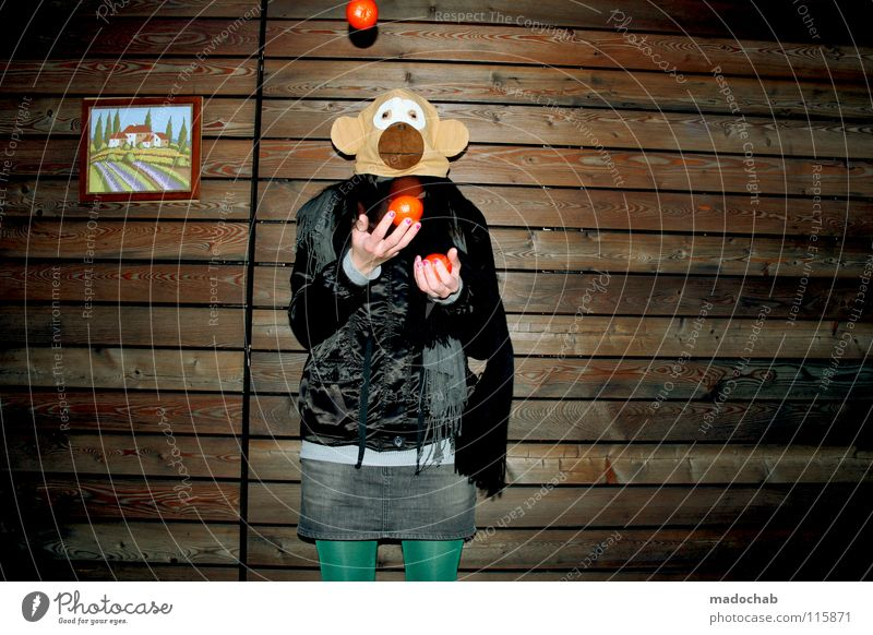 Young woman with monkey mask juggles mandarins like in a circus Monkey theatre Woman Umbrella Cap Cold Emotionally cold Impersonal Belt Carnival Good mood