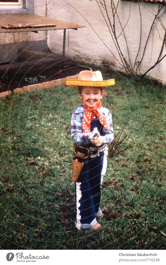 Young Gun Cowboy Cowboy hat Carnival Ahoy Moustache Happiness Child Grass Green Weapon Image type and genre Western Handgun Toddler Hero Helau alaaf Laughter