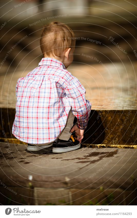 concentrated Toddler Boy (child) Infancy Body Head Back Arm Fingers Legs Feet 1 Human being 1 - 3 years Water Spring Shirt Jeans Sneakers Fountain Observe
