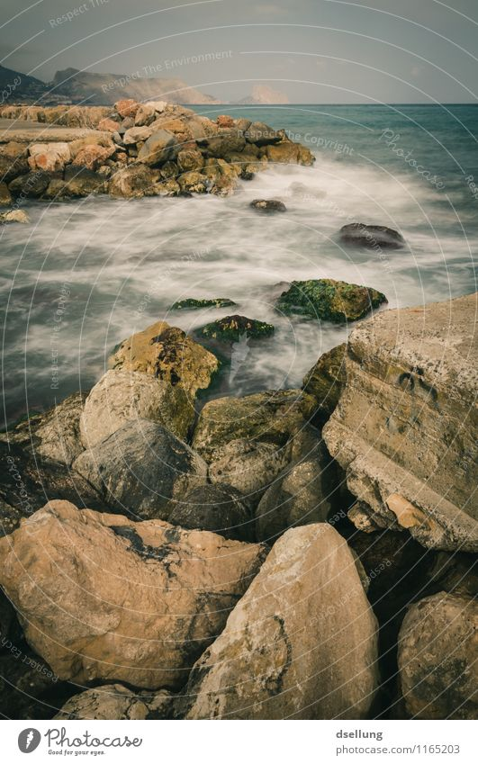 gentle surf. Environment Nature Landscape Elements Earth Water Sky Clouds Rock Waves Coast Ocean Thin Sharp-edged Cold Maritime Wet Strong Gloomy Brown Gray