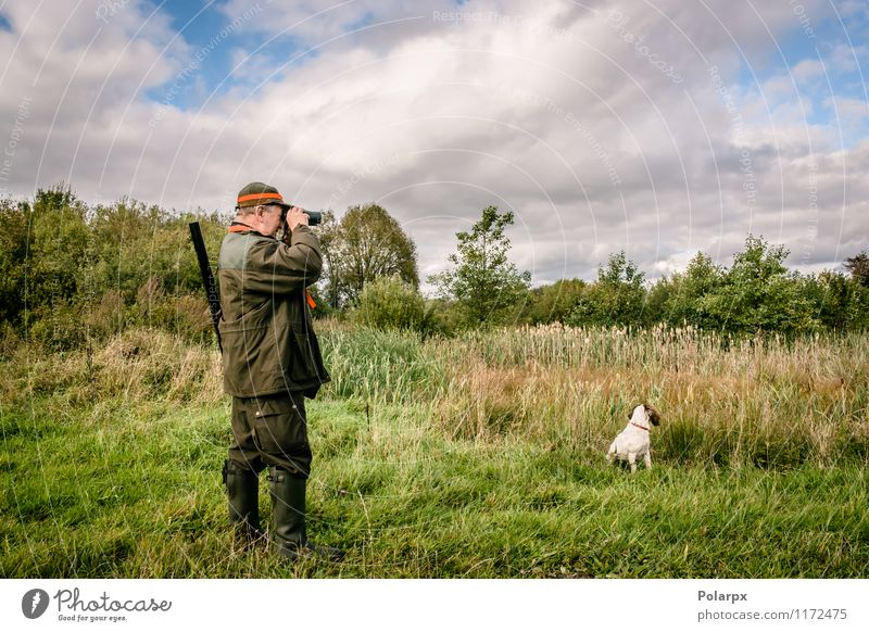 Hunter with binculars Relaxation Leisure and hobbies Hunting Sports Human being Man Adults Nature Landscape Autumn Jacket Hat Dog Binoculars Observe Stand Wild