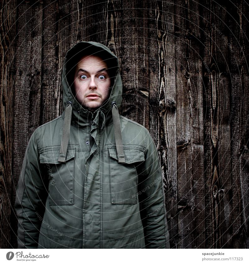 I see something you can't see! Man Portrait photograph Freak Wall (building) Wood Winter Cold Fear Eerie Panic Joy Structures and shapes Hooded (clothing)
