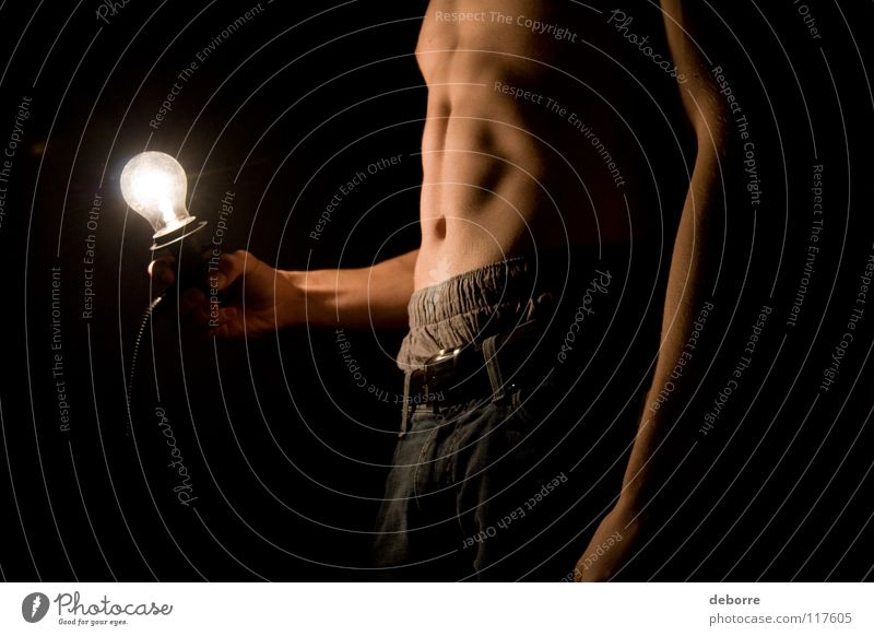 Young man posing topless in the dark with lightbulb. Close-up Electric bulb Fellow Light Naked Black Man Arm poor Stomach Legs belly Dude Guy Skin Jeans nude