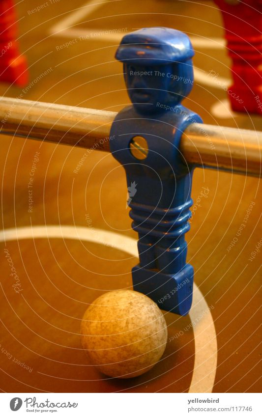 The captain. Table soccer Soccer player Sports Playing Ball Sphere Blue Piece Screw Center circle Front view Close-up Rod Perspective Shallow depth of field