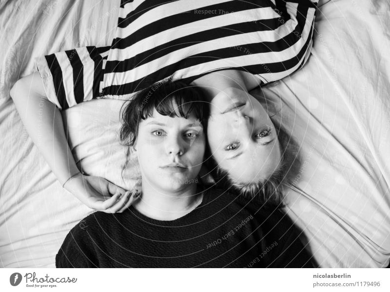 Two young women lie casually together on a bed with heads and look into the camera Couple already Feminine Love Friendship Young woman Harmonious Well-being