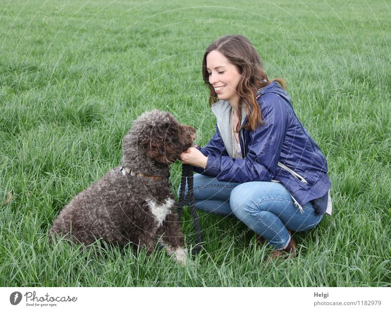young woman with long brunette hair squats smiling on a meadow and looks at her dog Human being Feminine Young woman Youth (Young adults) Adults 1 18 - 30 years