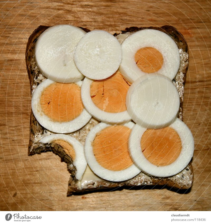 A bite Sandwich Bread Dinner Breakfast Chopping board Yolk Meal Nutrition Food Circle Geometry Part Attempt Full Butter Egg egg sandwich Haircut yellowish-white