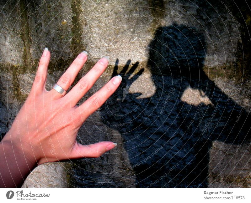 Who's afraid of the black man? Colour photo Light Shadow Hand Fingers Wall (barrier) Wall (building) Stone Threat Dark Creepy Gray Black Protection Concern Fear