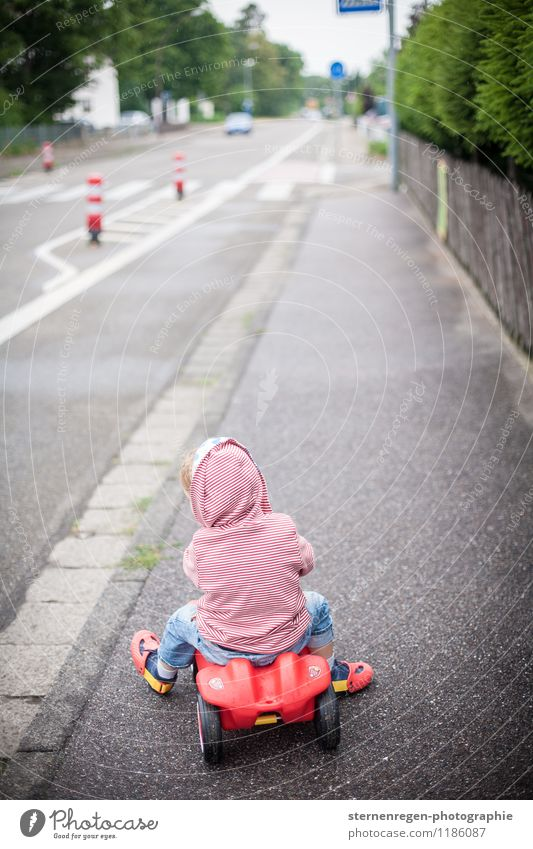 road traffic Bobbycar Child Childhood memory Toddler Car Street Sidewalk Footpath Driving Playing Red Toys Traffic cone Pylon Hooded (clothing)