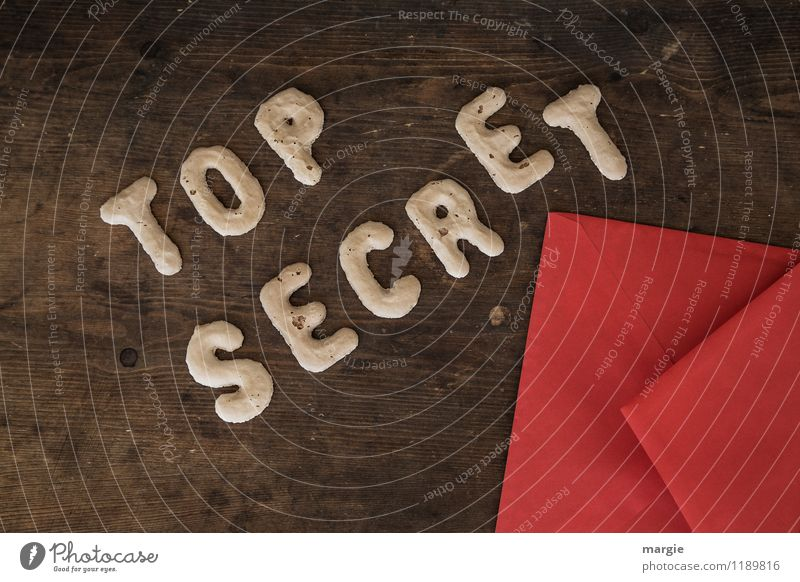 The letters TOP SECRET with a red envelope on a rustic wooden table Education Examinations and Tests Work and employment Office work Economy Industry Trade