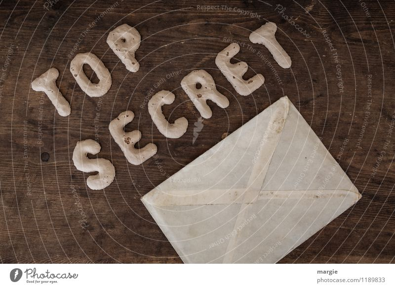 The letters TOP SECRET with an envelope on a rustic wooden table Examinations and Tests Office work Workplace Economy Industry Services Media industry