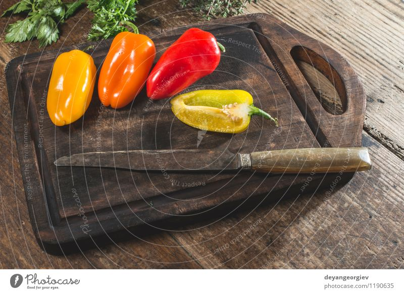 Multicolored peppers on wood Vegetable Fruit Nutrition Eating Vegetarian diet Fresh Natural Juicy Yellow Green Red White Colour food knife background bell