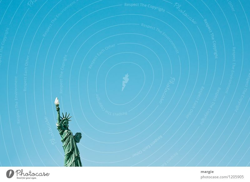 A Statue of Liberty in front of a blue sky in landscape format Art Sculpture Manmade structures Tourist Attraction Landmark Monument Statue of liberty Sign
