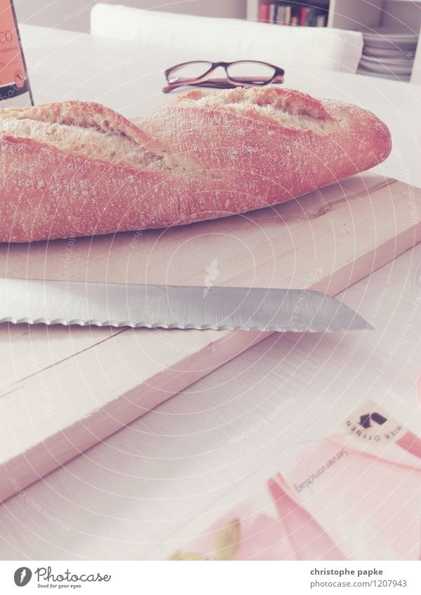 Baguette with knife on board on table Food Bread Nutrition Breakfast Knives Living or residing bread knife Eyeglasses Wooden board Table Colour photo