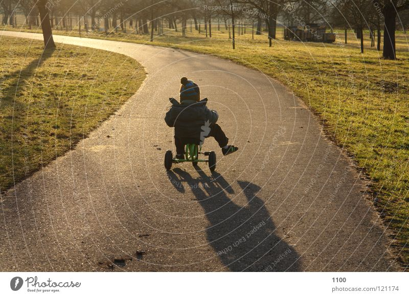 towards the sun Tricycle Driver Child Evening sun Sunset Vehicle Means of transport Footwear Musculature Boy (child) Street Lanes & trails tree meadow