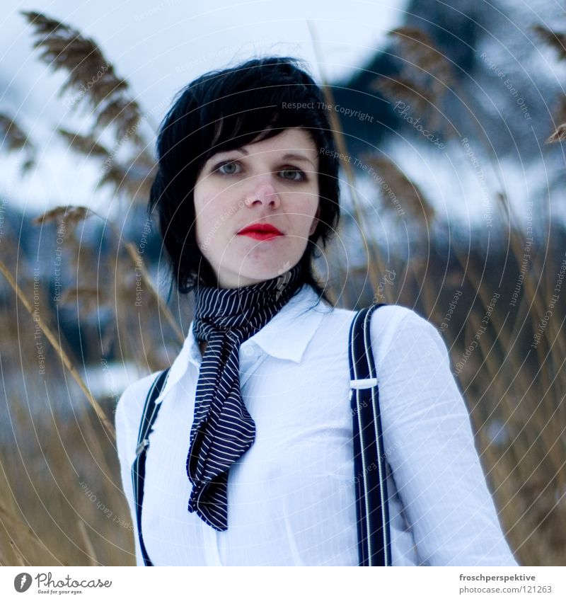 Don't look at me like that. Woman Make-up Wearing makeup Black-haired Fairy tale Suspenders Fir tree Switzerland Common Reed Winter Cold Gray clouds Lake Freeze