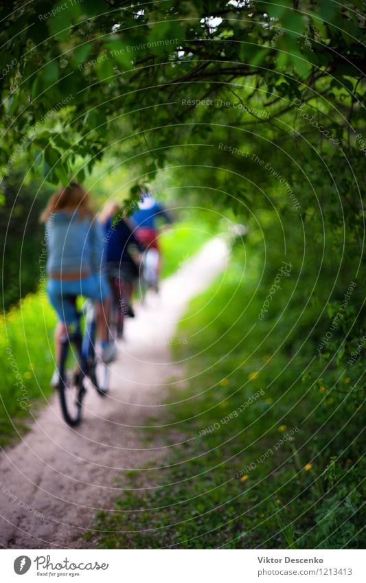 Cyclists in bright clothes riding through the forest path Design Vacation & Travel Summer Cycling Art Nature Flower Park Forest Baltic Sea Transport Street