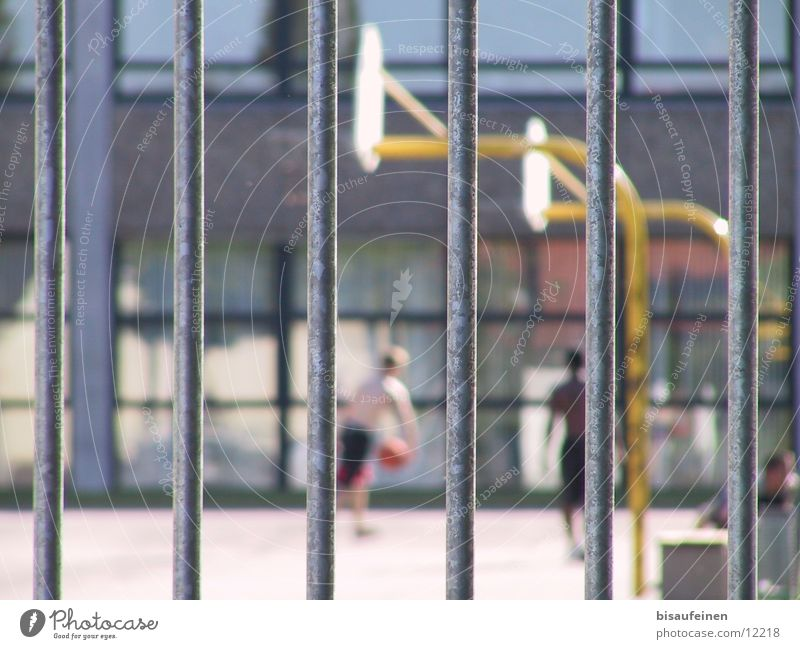 imprisoned Playing Sports Schoolyard Grating Basketball basket Fence Captured tribble Colour photo Multicoloured Exterior shot Day Blur Shallow depth of field