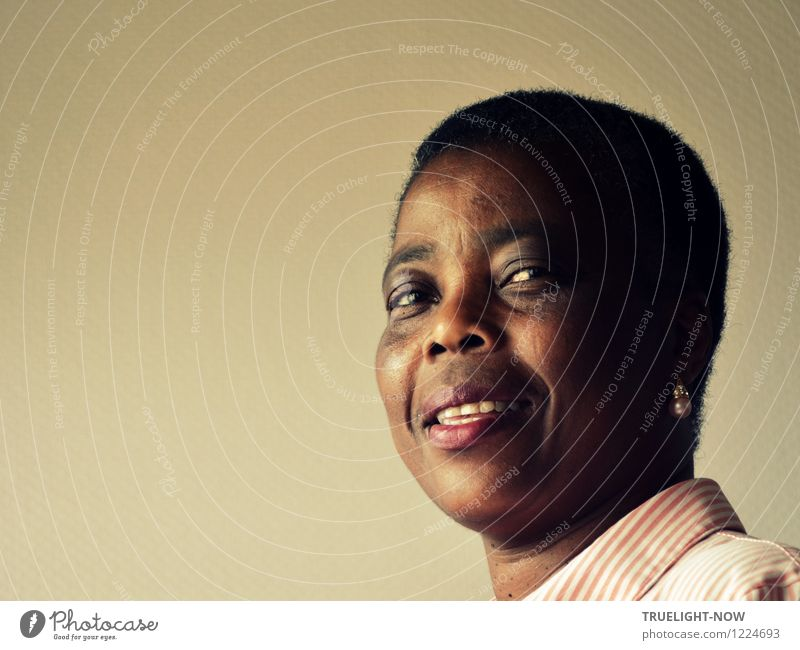 Beautiful, strong African woman in half profile with short hairstyle, pearl on ear and white and pink striped blouse looks smiling into the camera with slightly opened mouth