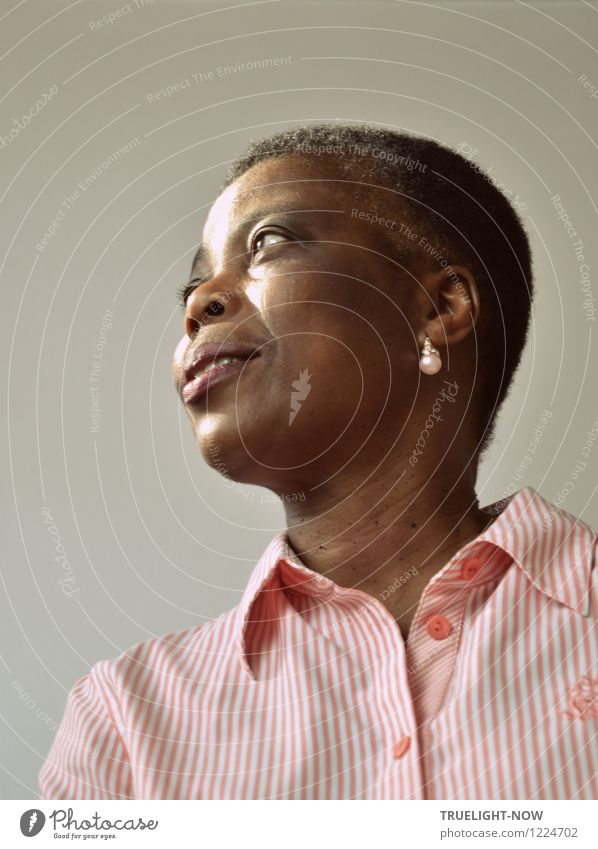 Beautiful African woman with short hairstyle, a white pearl on the ear and in a white pink striped elegant blouse looks in half profile with slightly opened mouth sideways into the distance