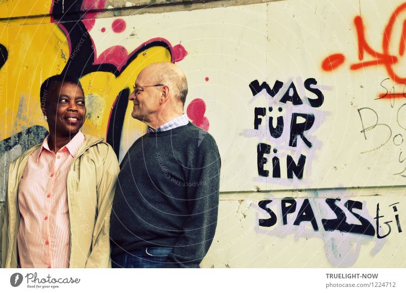 Beautiful coloured African woman and white senior form a couple with eye contact, standing close together in front of a wall painted with graffiti and the text WHAT FOR FUN, smiling lovingly into each other's eyes