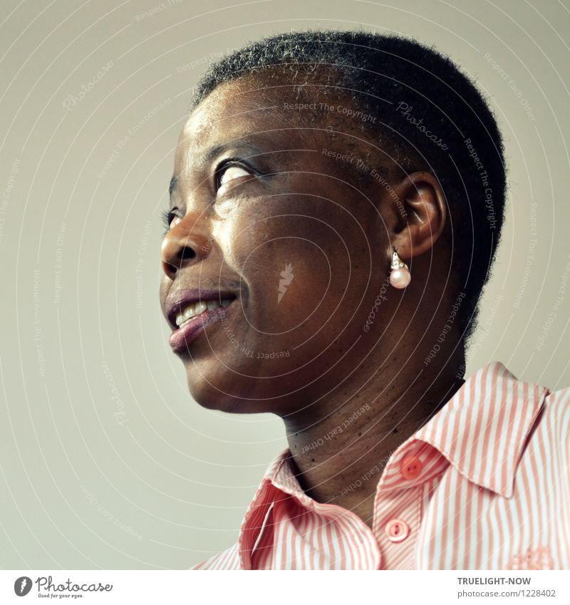 Beautiful African woman from Togo with very short hair, slightly opened mouth, one earring with pearl in a white and pink striped fine shirt with collar from below in half profile