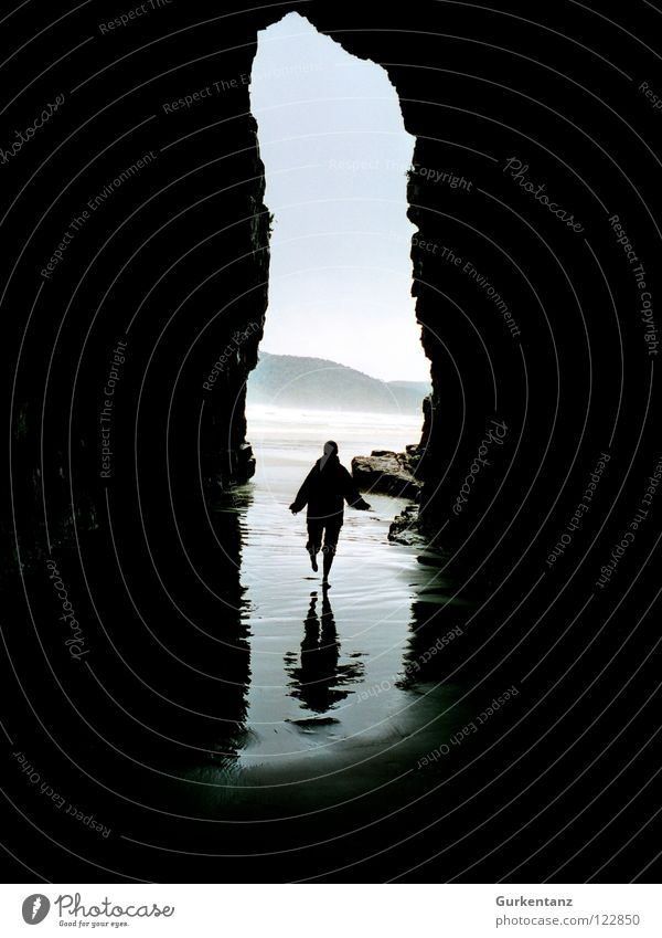 shadow running New Zealand South Island Cave Ocean Beach Reflection Walking Wet Low tide Tide Coast Black & white photo Mountain cavern Cathedral cathedral cave