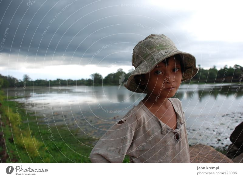 Calm before the storm Child Girl Arm Water Gale Rain Thunder and lightning River Landmark Monument Hat Poverty Curiosity Sadness Longing Cambodia Angkor Wat