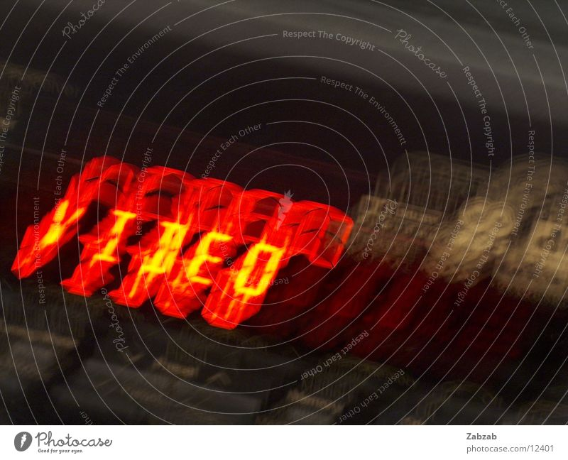 video Video Red Digits and numbers Light Electrical equipment Long exposure Letters (alphabet) Yellow Black Dark Television DVD-ROM Interior shot Entertainment