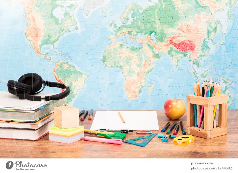 School accessories on desktop with map at background School Fruit Book Study Apple Desk Headphones Pen Tool Workplace Map Piece of paper Pencil Crayon Object photography Scissors