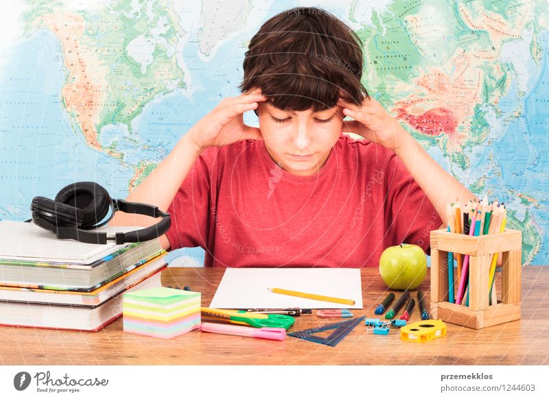 Young boy thinking about his homework Apple Desk Education Study Schoolchild University & College student Workplace Tool Human being Boy (child) 1 8 - 13 years