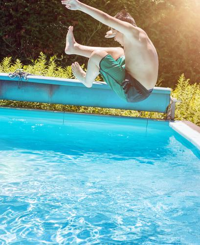 Jump into the water Lifestyle Summer Sun Swimming pool Child Boy (child) Water Sunlight Flying Sports Esthetic Athletic Authentic Wet Positive Blue