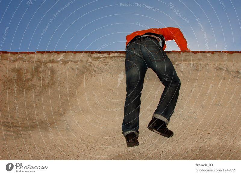 Prison break Wall (barrier) Wall (building) Man Yellow Red Back-light Cyan Sky blue Footwear Pants Sweater Outbreak Drift Above Captured Confine Narrow Cramped