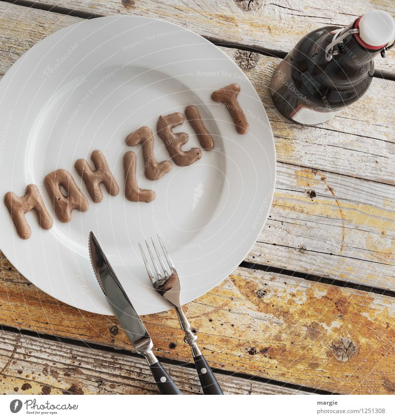 On a rustic wooden table a plate with the letters MAHLZEIT, knife and fork and a bottle of beer Food Nutrition Lunch Dinner Picnic Vegetarian diet Diet