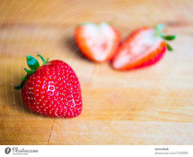 Strawberry on a wooden board Fruit Nutrition Organic produce Vegetarian diet Healthy Eating Summer Fresh Juicy Sweet Green Red background Berries blured cutted