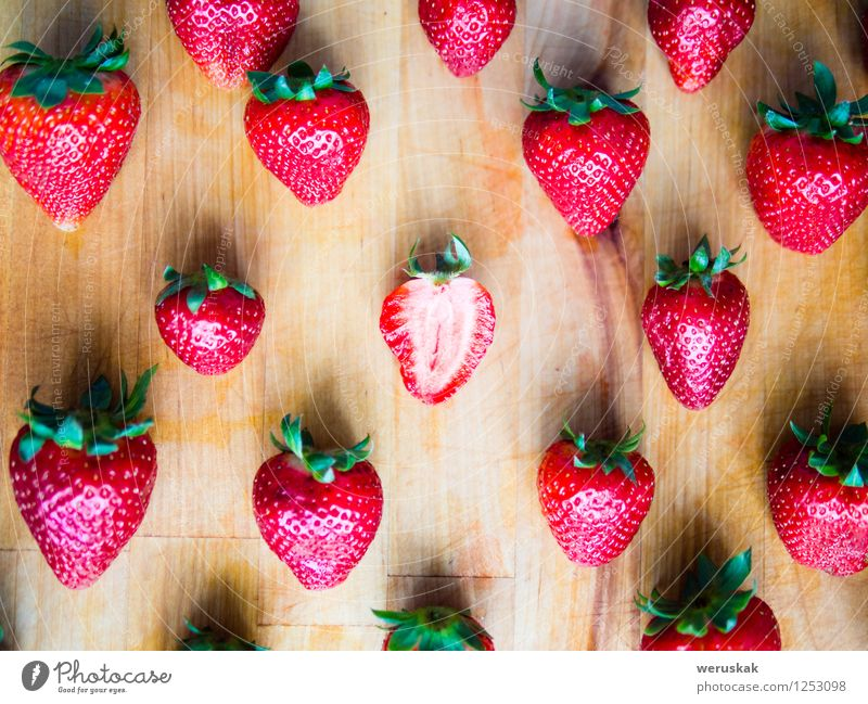 One cutted strawberry in an srranged pattern of strawberries on Green Summer Red Loneliness Healthy Eating Exceptional Fruit Design Decoration Fresh Nutrition