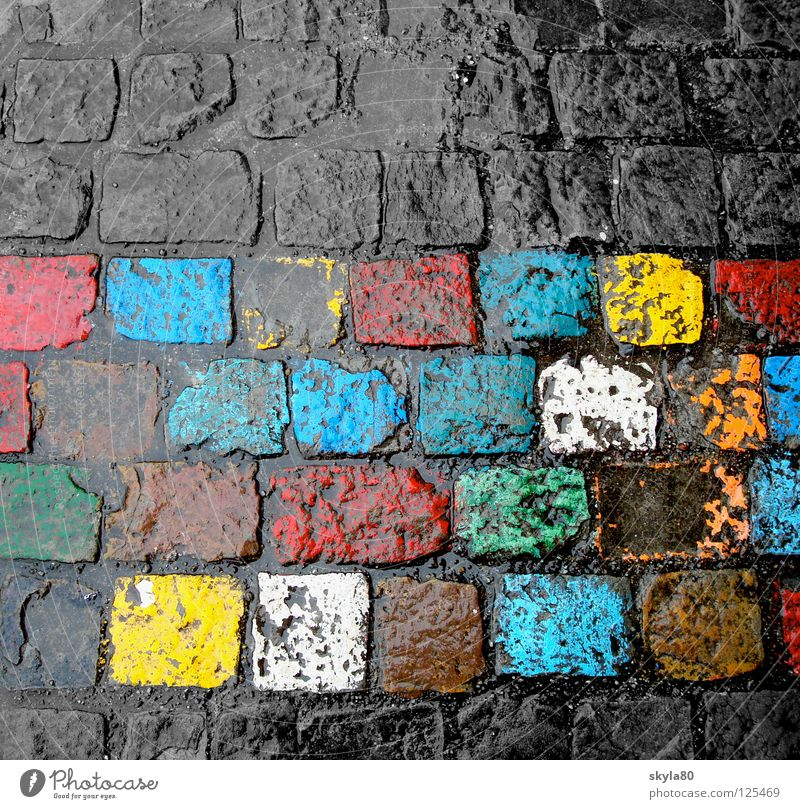 Everyday colour Town Multicoloured Yellow Red Green Rainbow Reflection Glittering Wet February Colour Cobblestones Stone Floor covering playground Blue