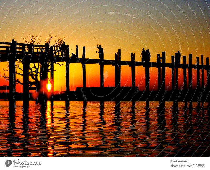 Burmese Bridge Myanmar Mandalay Teak Wood Wooden bridge Asia Dusk Lake Back-light Light Red Tree u-leg Pole Evening Water Shadow Silhouette Sun Human being