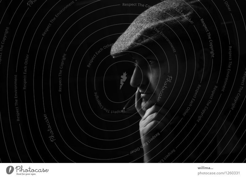 Young man with slider cap in front of black HG chin on hand, profile Man Adults Head Hand sliding cap Peaked cap Dark Black Meditative Rest on Observe Think
