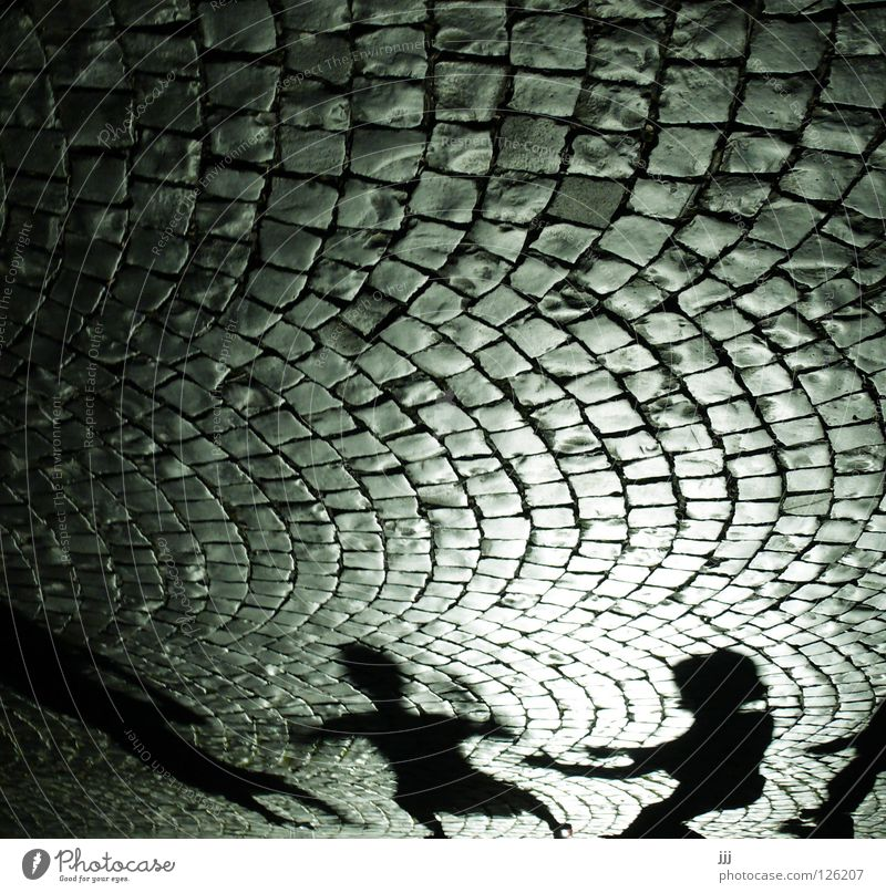 street scene Cobblestones Light Silhouette Playing Black Dark Cone of light Cinema Group Fear Panic Shadow Arch Stone Street Human being Arm Catch Dance Hat