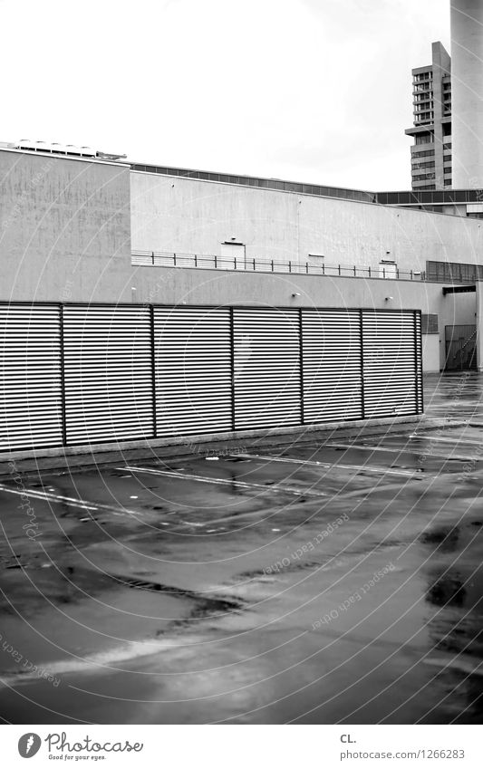 Somewhere Bad weather Rain Town High-rise Places Parking garage Building Wall (barrier) Wall (building) Transport Parking lot Gloomy Black & white photo