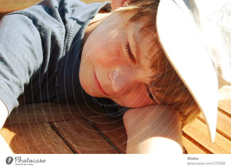sleeping cap Boy (child) Masculine Child Sleep Slouch Baseball cap Dazzle Summer Wood Table Watercraft Human being Lie Fatigue Relaxation Grinning