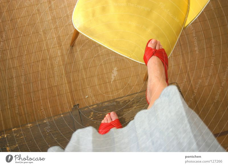 Woman in red open shoes climbs on yellow chair Footwear Summer Sandal Stand wood Chest Ascending Far-off places Conquer Yellow Playing Children's game Room Red