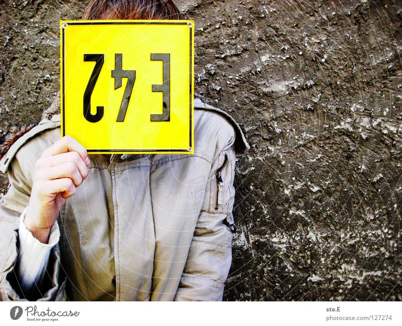 blonde Fellow Man Wall (building) Wall (barrier) Pattern Plaster Signage Label Signs and labeling Blonde Stupid Hair colour Jacket Hand False Black Cold East