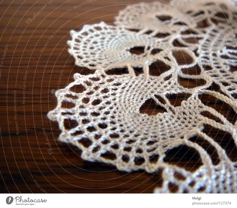 Close-up of a crocheted lace doily on a table Blanket Craft (trade) Effort Sewing thread Table Flat Round Warped Leisure and hobbies White Brown