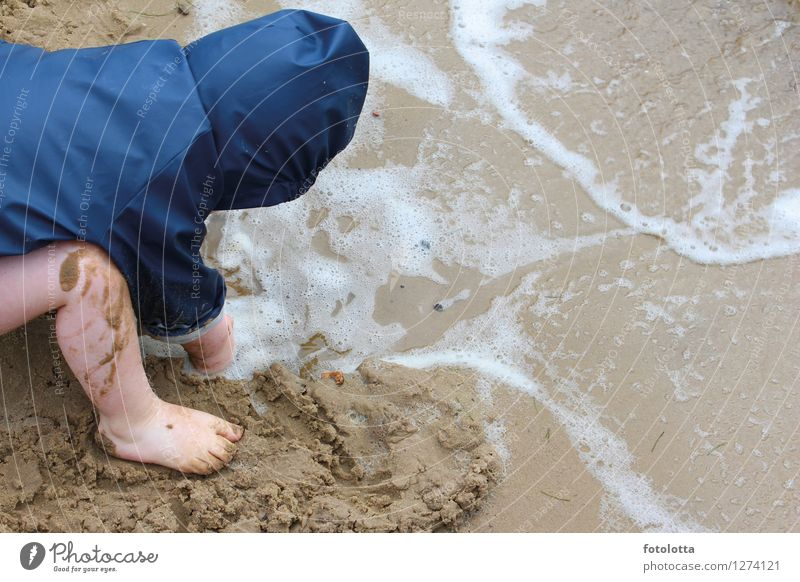 dig Joy Playing Muding Beach Toddler Legs Feet Nature Sand Water Waves River bank Rain jacket Wet Blue Beige slobbery Barefoot Wind Exterior shot Colour photo
