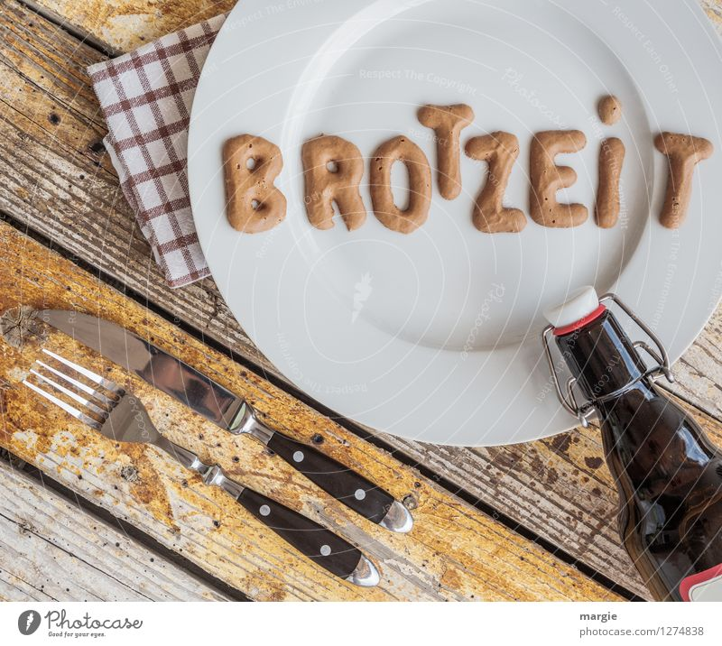 On a rustic wooden table a plate with the letters BREAD TIME, knife and fork, napkin and a bottle of beer Food Bread Brunch Nutrition Lunch Dinner Picnic